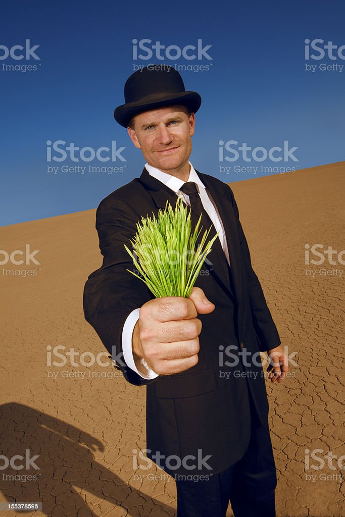 Businessman Offering Green Grass in the Desert stock photo