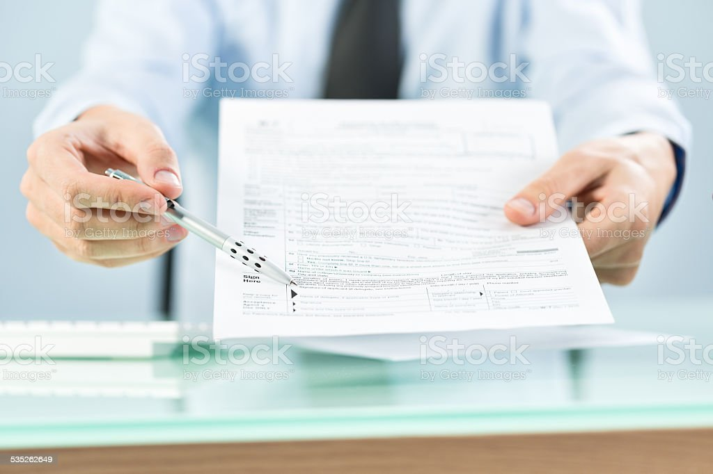 Businessman offering tax form for signing stock photo