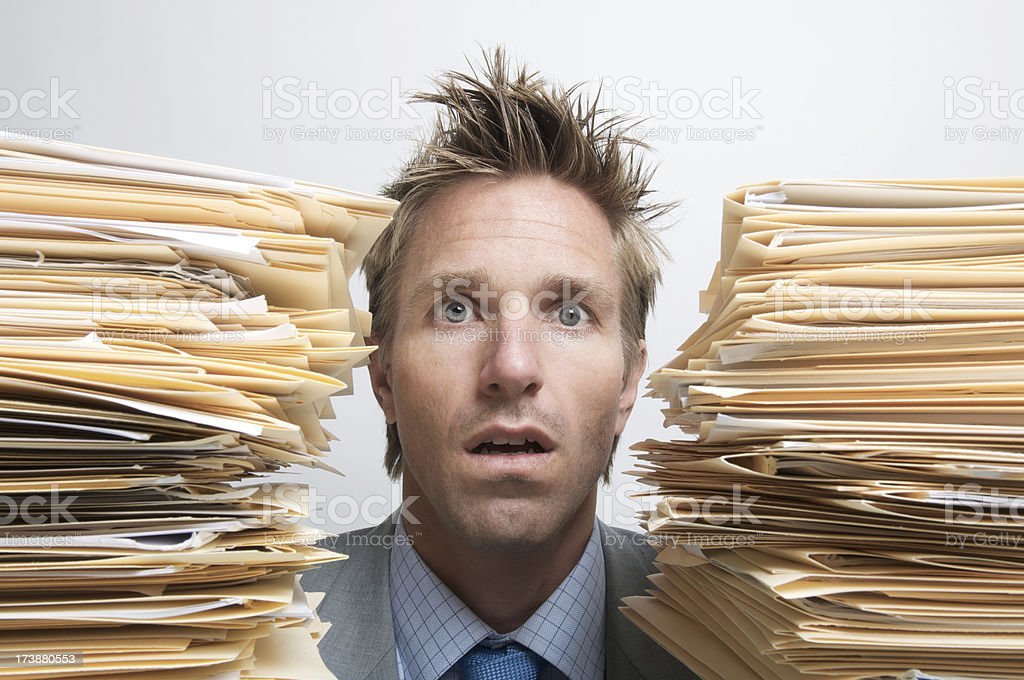 Businessman Office Worker Sits Dazed Between Piles of Paperwork Files stock photo