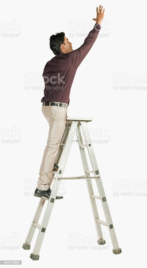 Businessman on a ladder stock photo