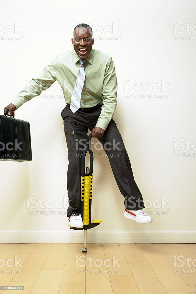 Businessman on a pogo stick stock photo