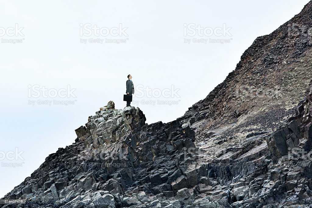 Businessman On A Rocky Slope Looks At The Challenges Ahead stock photo