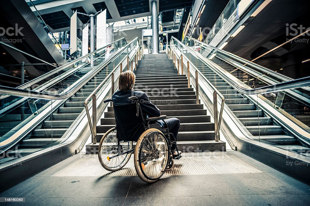 Businessman on a wheelchair against modern stairs stock photo
