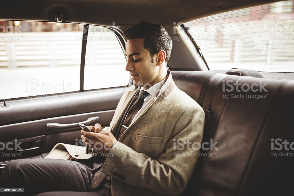 Businessman on a yellow cab text messaging stock photo