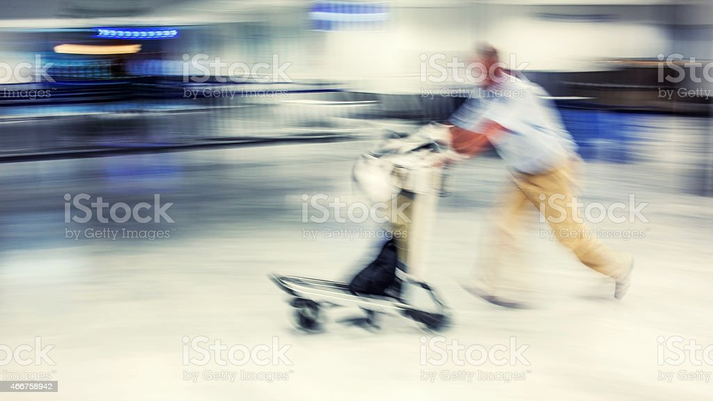 Businessman on airport with luggage cart stock photo