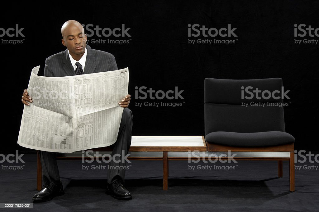 Businessman on bench seat reading newspaper stock photo