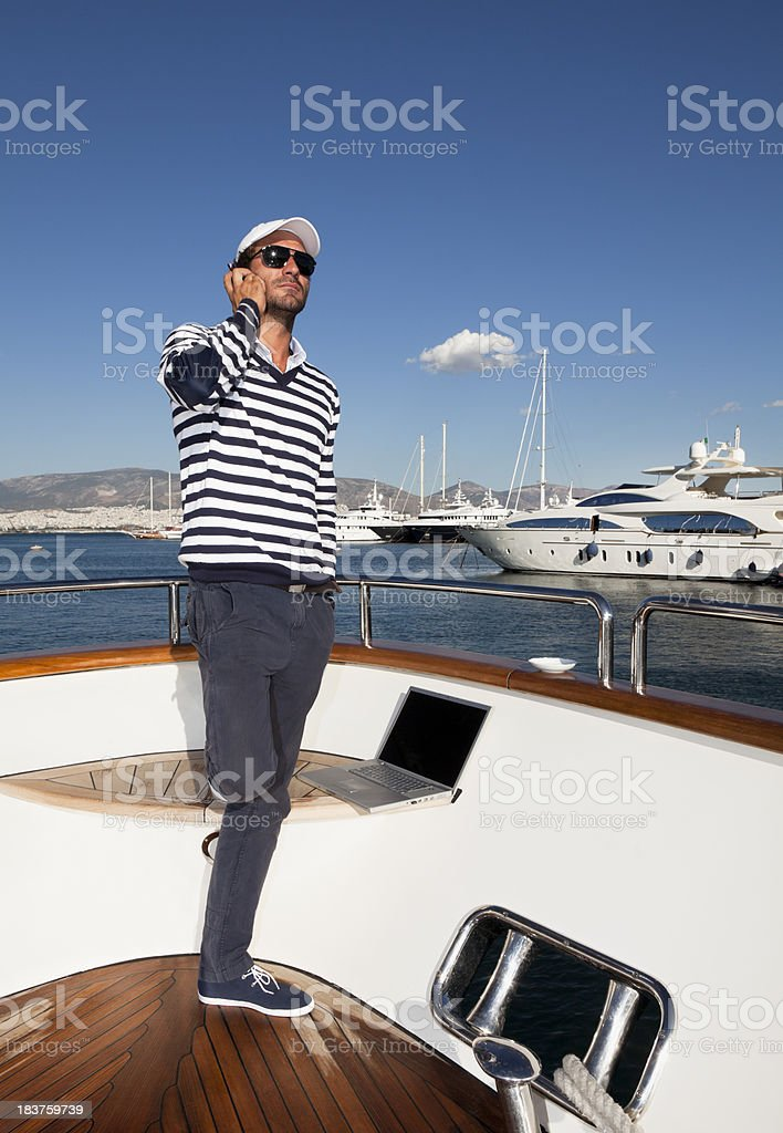 Businessman on board of the yacht. Phone discussion royalty-free stock photo