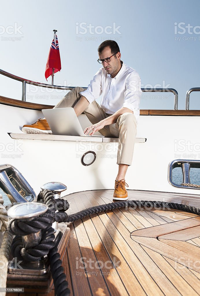 Businessman on board of the yacht reading e-mails royalty-free stock photo