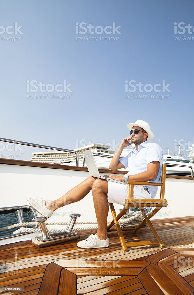 Businessman on board of the yacht. Relaxing. Using laptop royalty-free stock photo