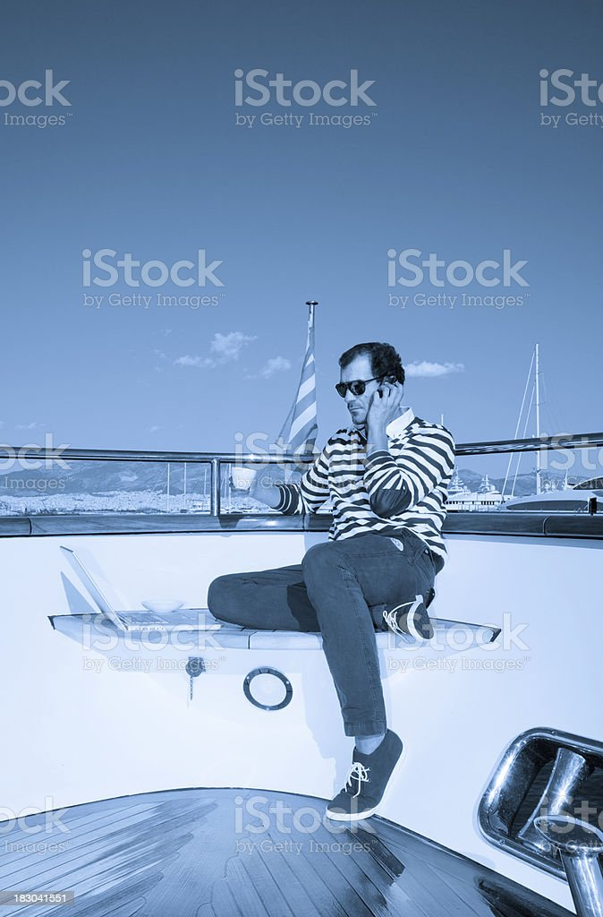 Businessman on board of the yacht talking and drinking coffee royalty-free stock photo