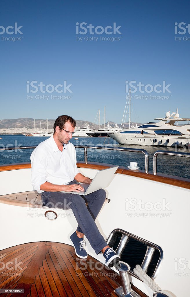 Businessman on board of the yacht working and having coffee royalty-free stock photo