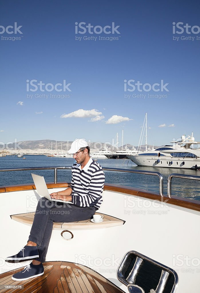 Businessman on board of the yacht working with laptop stock photo