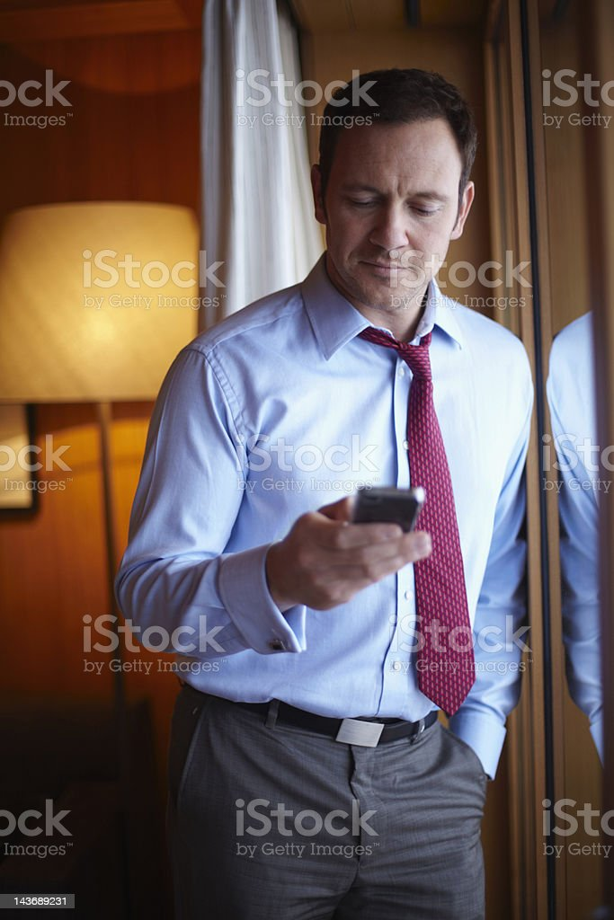 Businessman on cell phone in hotel room royalty-free stock photo