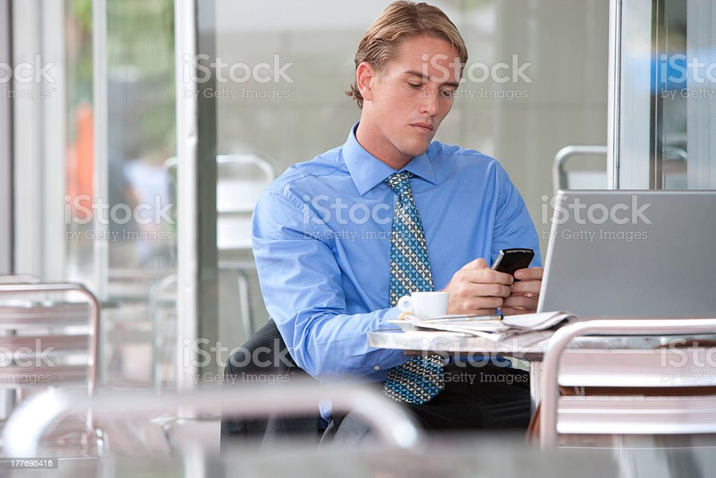 Businessman on cellular phone at outdoor patio table royalty-free stock photo