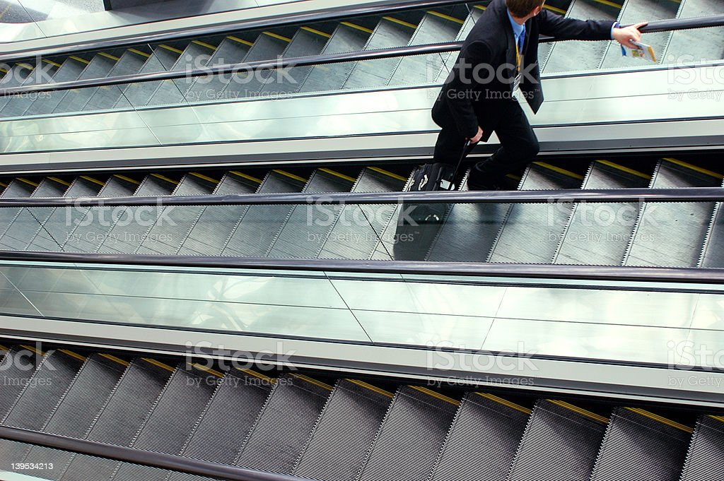 businessman on escalator - a series royalty-free stock photo