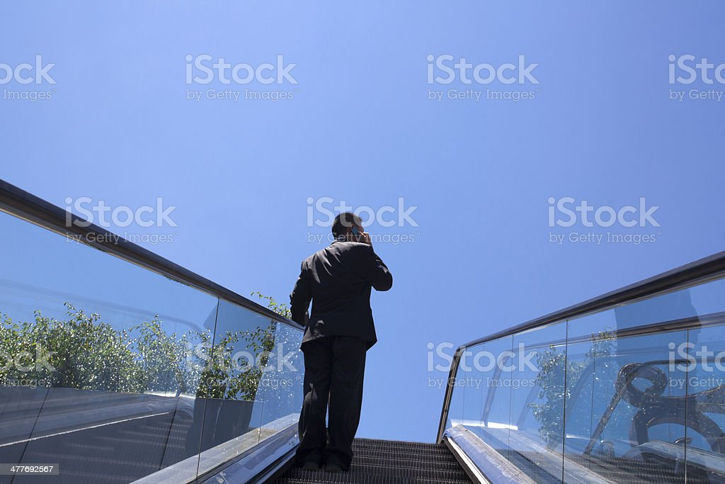 Businessman on Escalator Using Phone royalty-free stock photo
