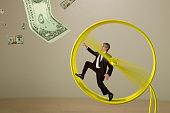 Businessman on hamster wheel chasing money success