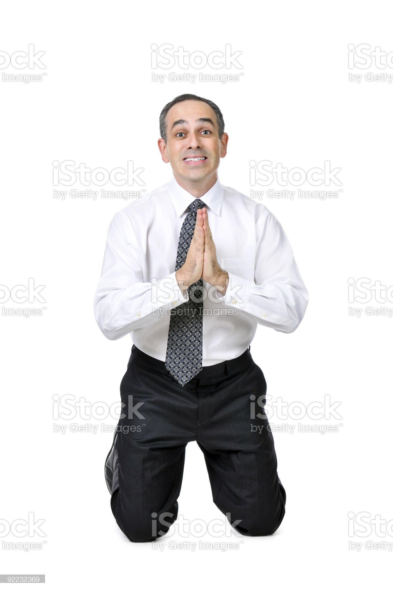 Businessman on his knees, pleading on a white background royalty-free stock photo