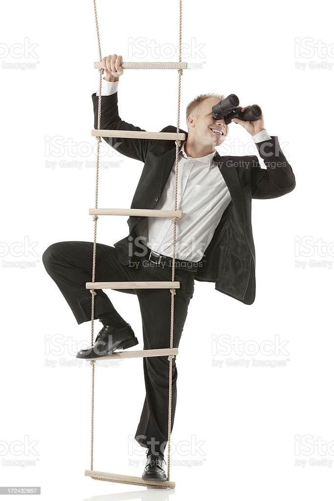 Businessman on ladder looking through binoculars stock photo