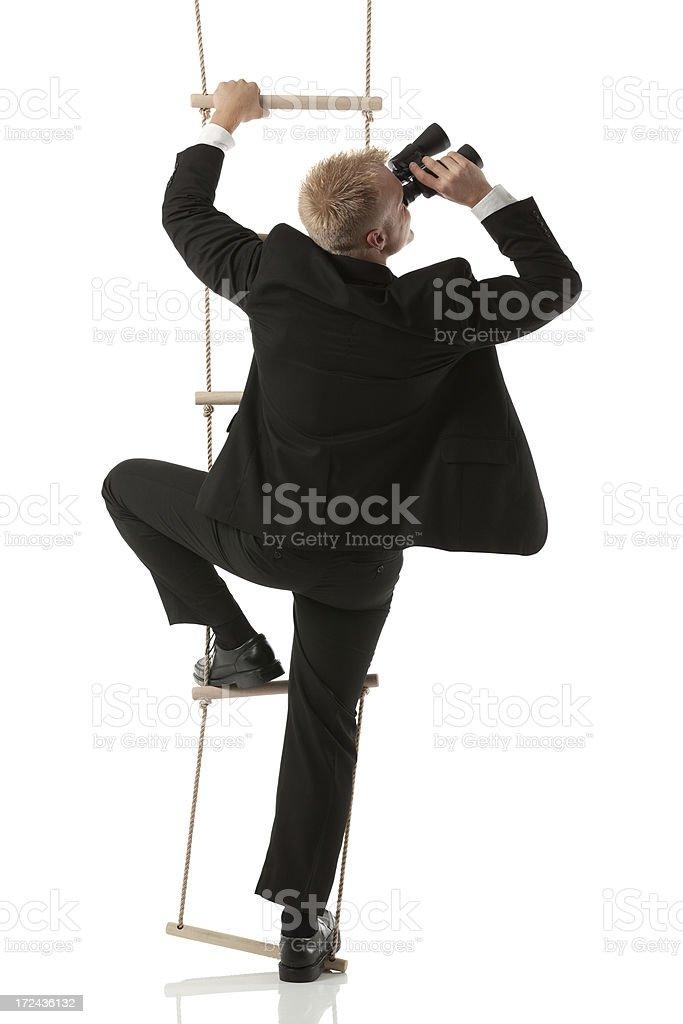 Businessman on ladder looking through binoculars royalty-free stock photo