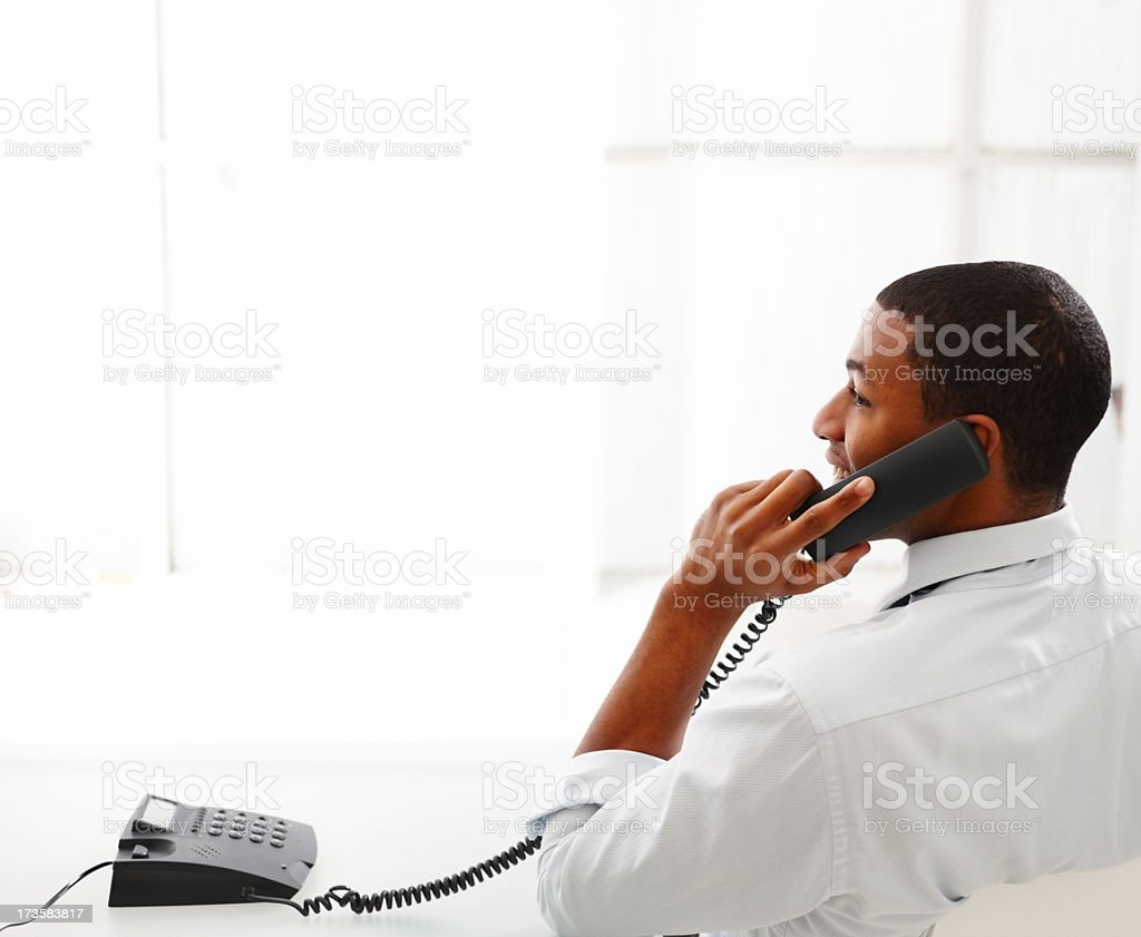 Businessman on landline telephone in white office royalty-free stock photo