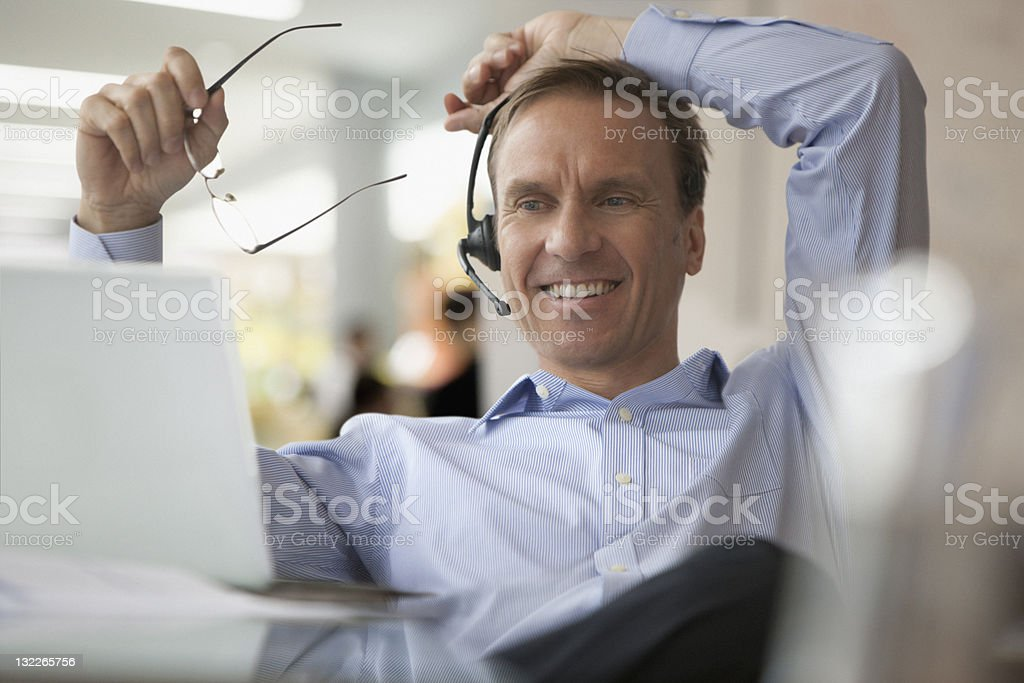 Businessman on laptop and earpiece royalty-free stock photo
