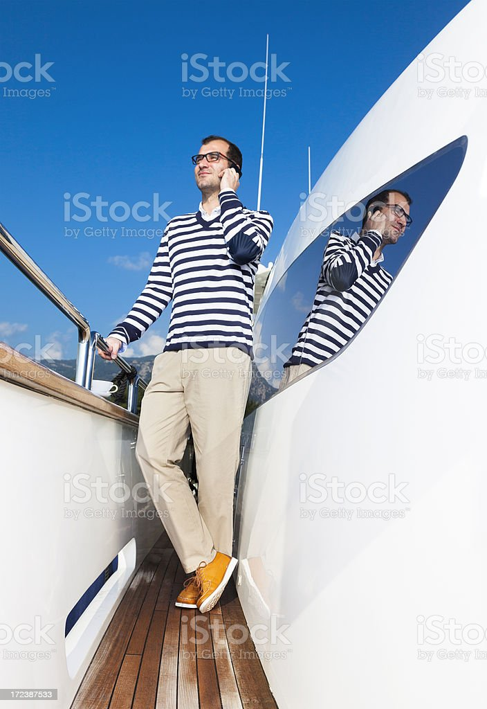 Businessman on Luxury Yacht. Talking business. Mobile phone royalty-free stock photo