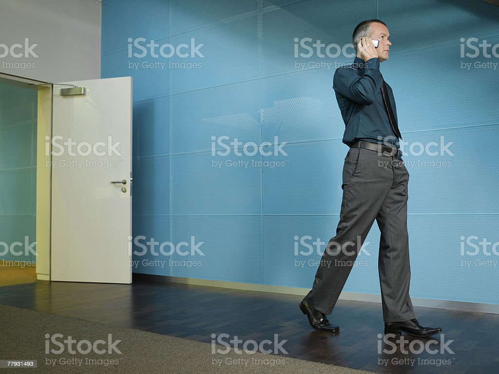 Businessman on mobile phone in blue office royalty-free stock photo