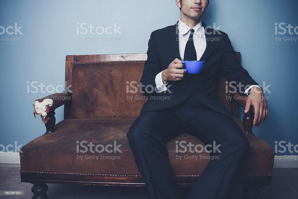 Businessman on old vintage sofa drinking coffee or tea royalty-free stock photo