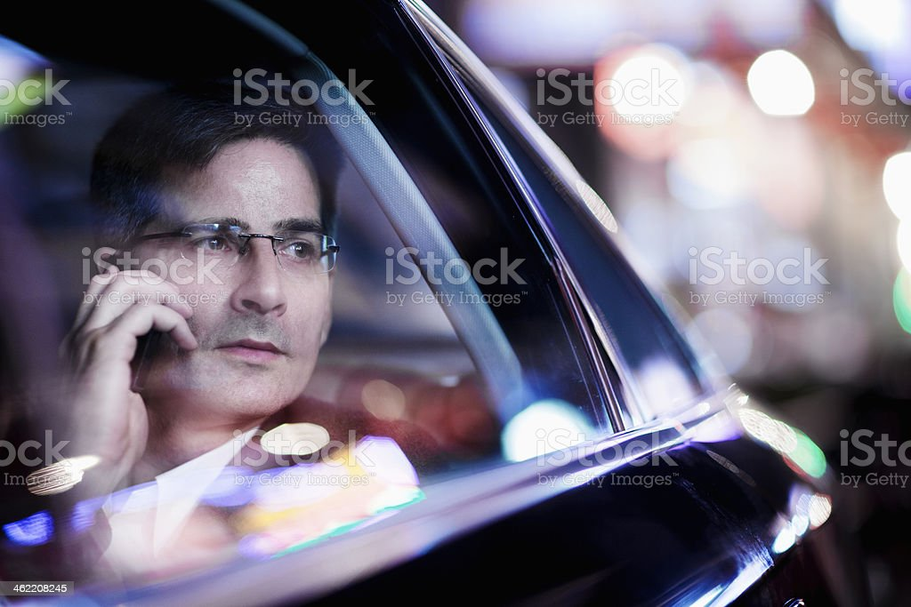 Businessman on phone and looking out car window at night stock photo