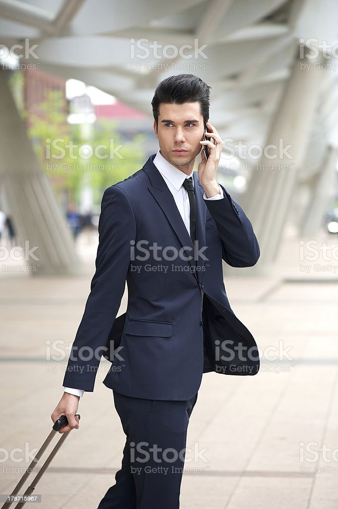 Businessman on phone and traveling with bag royalty-free stock photo