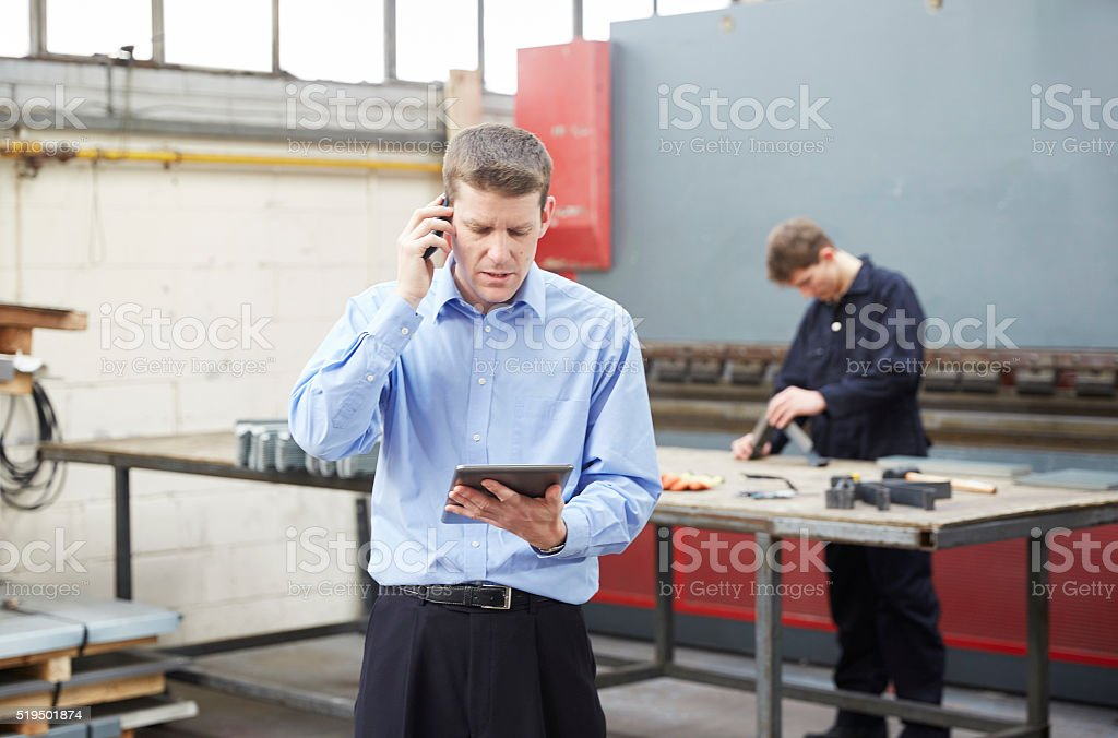Businessman on phone in steel fabrication factory stock photo