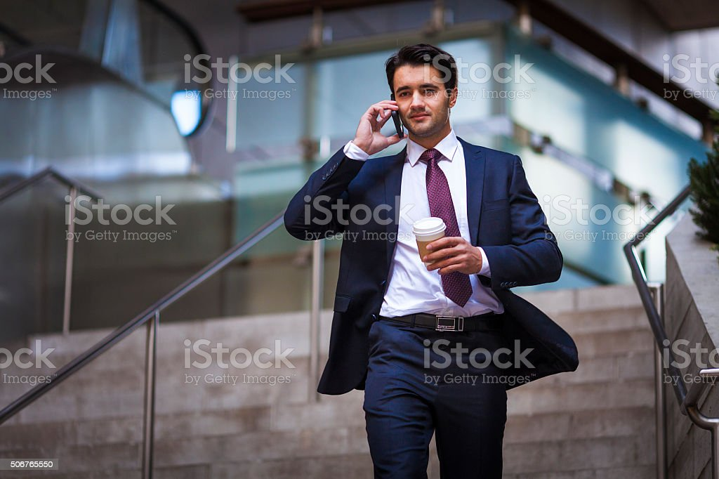 Businessman on phone running late stock photo