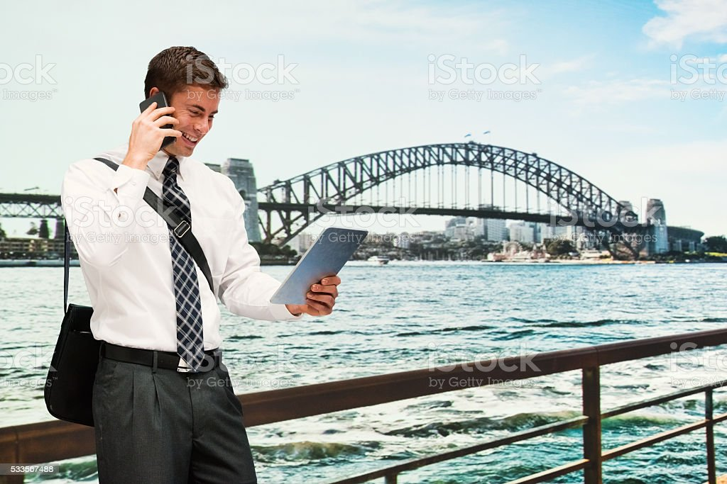 Businessman on phone while looking at tablet stock photo
