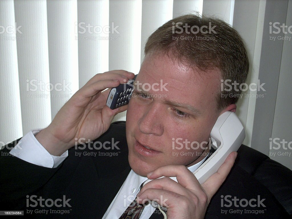 Businessman on phones:  Confused? stock photo