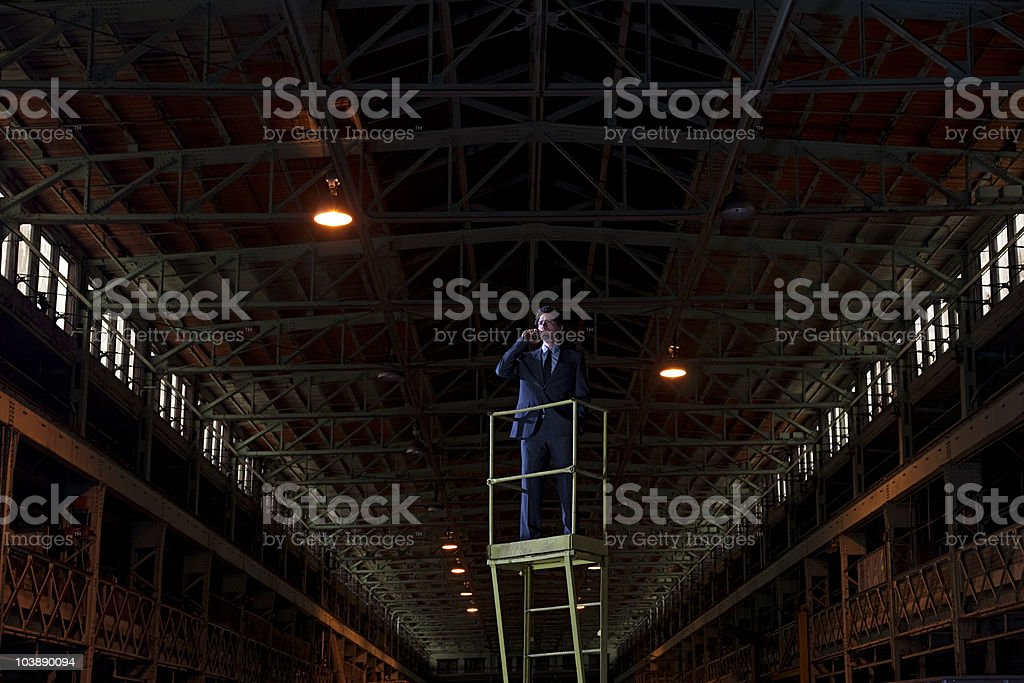 Businessman on platform in warehouse stock photo