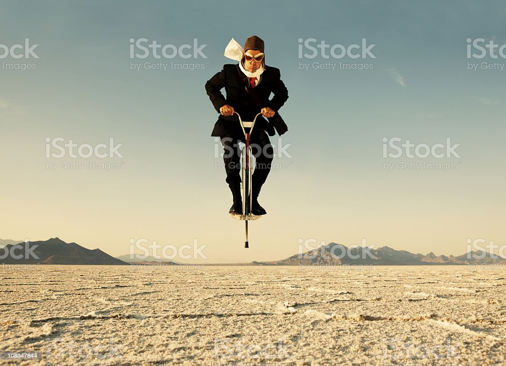 Businessman on Pogo Stick in Desert stock photo