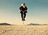 Businessman on Pogo Stick in Desert