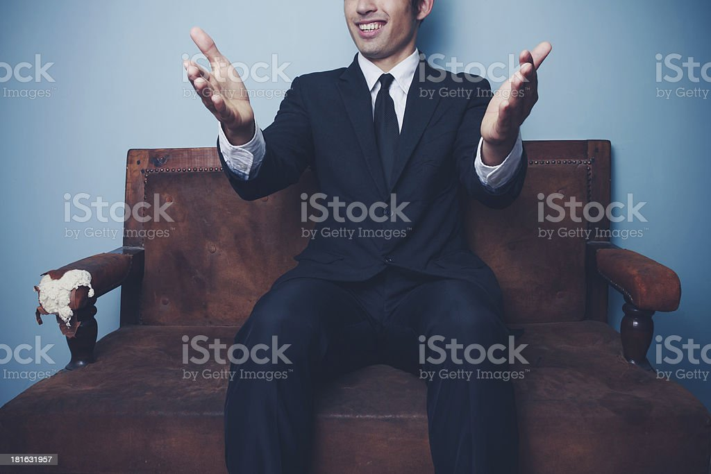 Businessman on sofa gesturing with his hands royalty-free stock photo
