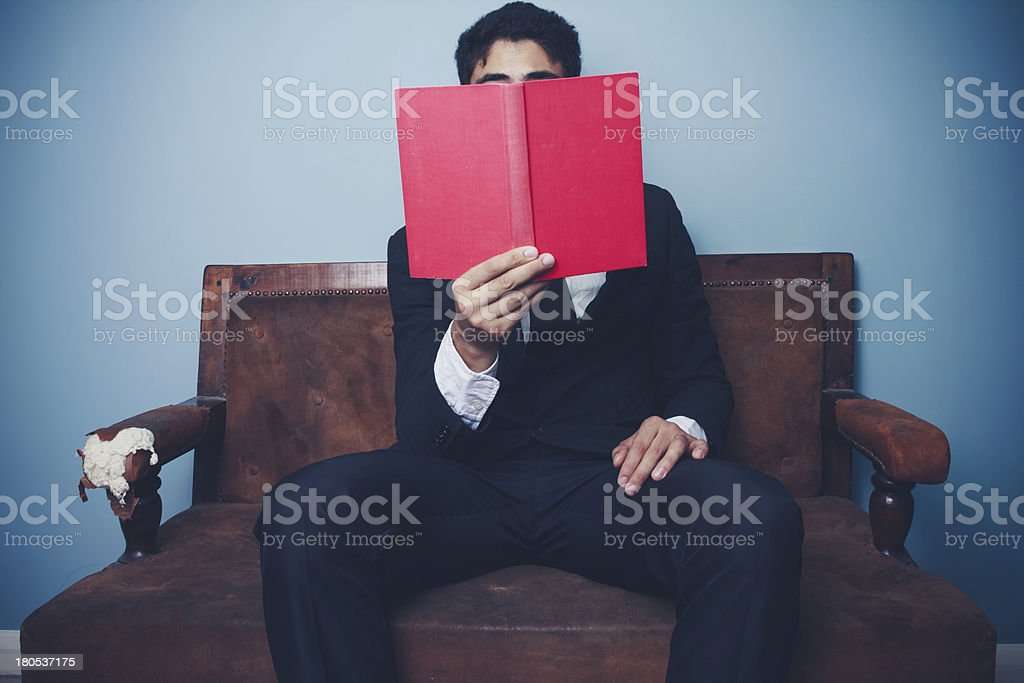 Businessman on sofa is reading communist red book royalty-free stock photo