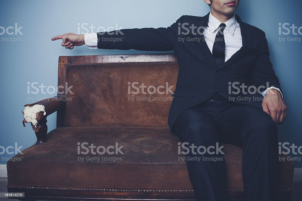 Businessman on sofa pointing left royalty-free stock photo