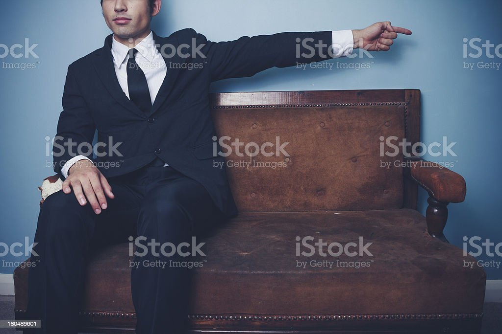 Businessman on sofa pointing right royalty-free stock photo