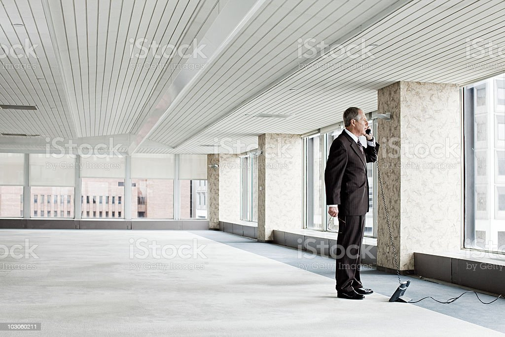Businessman on telephone in empty office stock photo