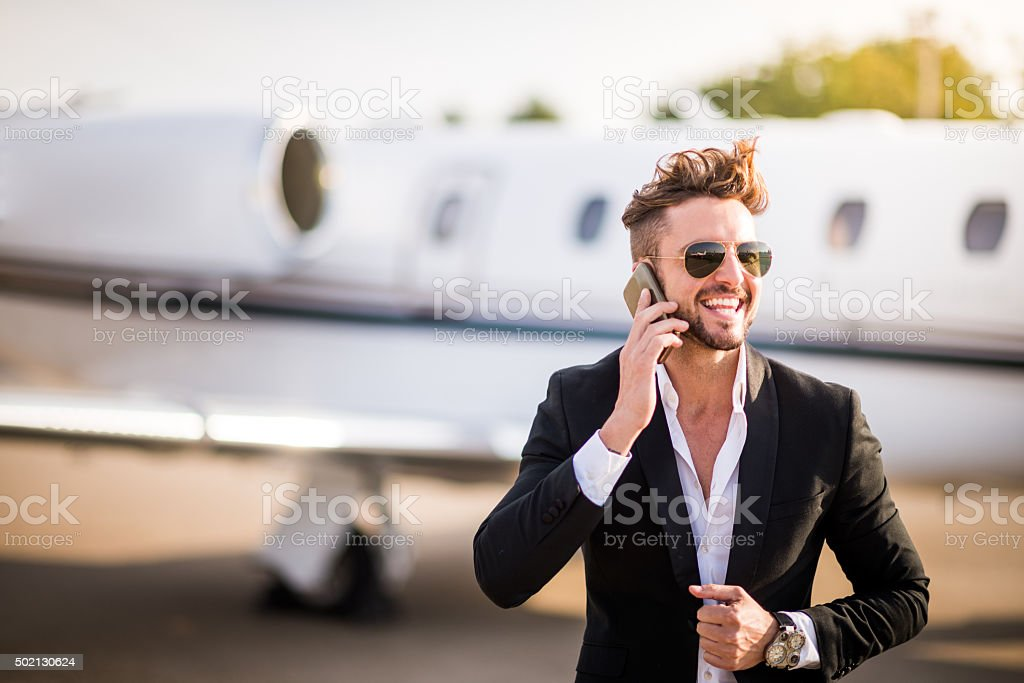 Businessman on the airport talking over mobile phone stock photo