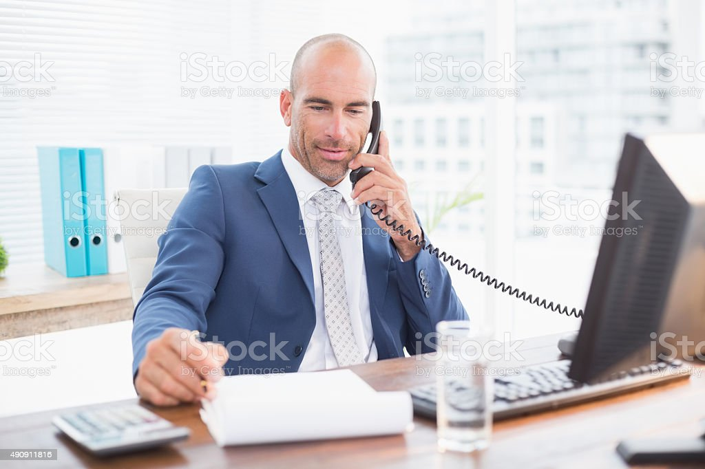 Businessman on the phone and writing notes stock photo
