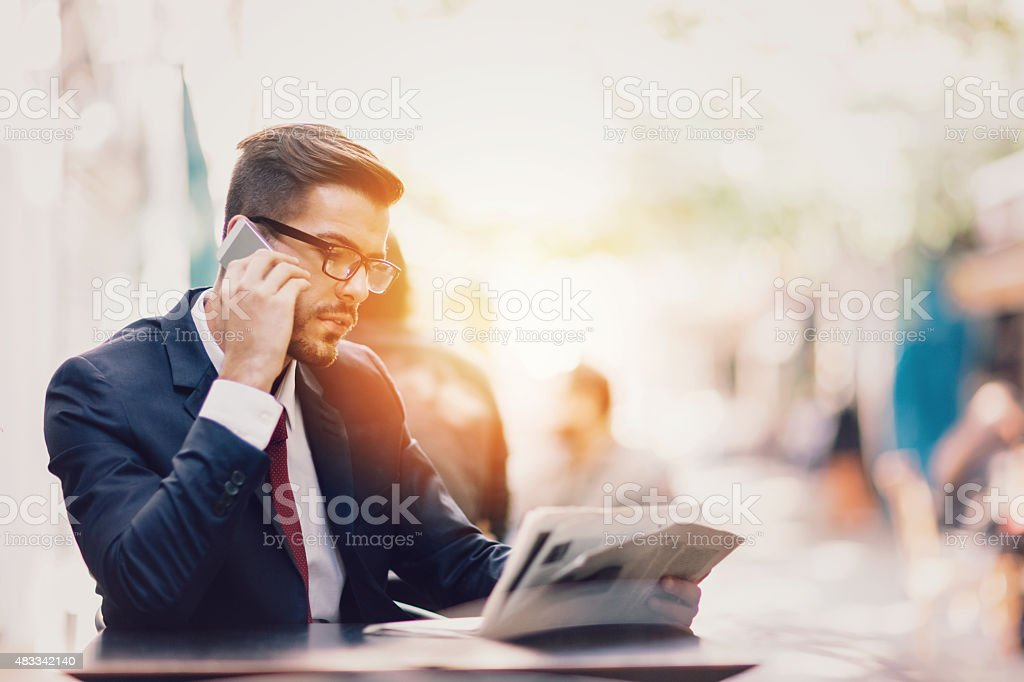 Businessman on the phone at a sidewalk cafe stock photo