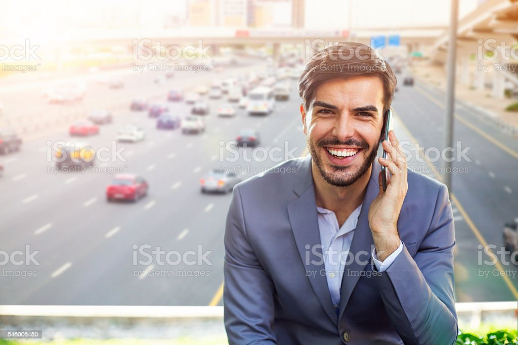 Businessman on the phone, Highway traffic in Dubai stock photo