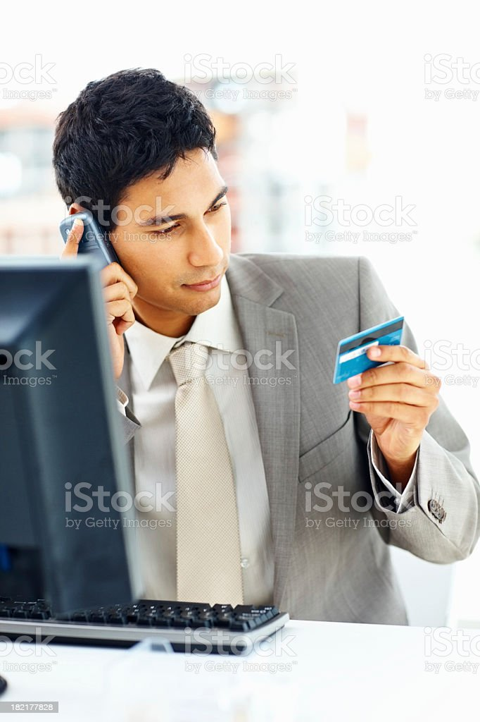 Businessman on the phone holding his credit card royalty-free stock photo