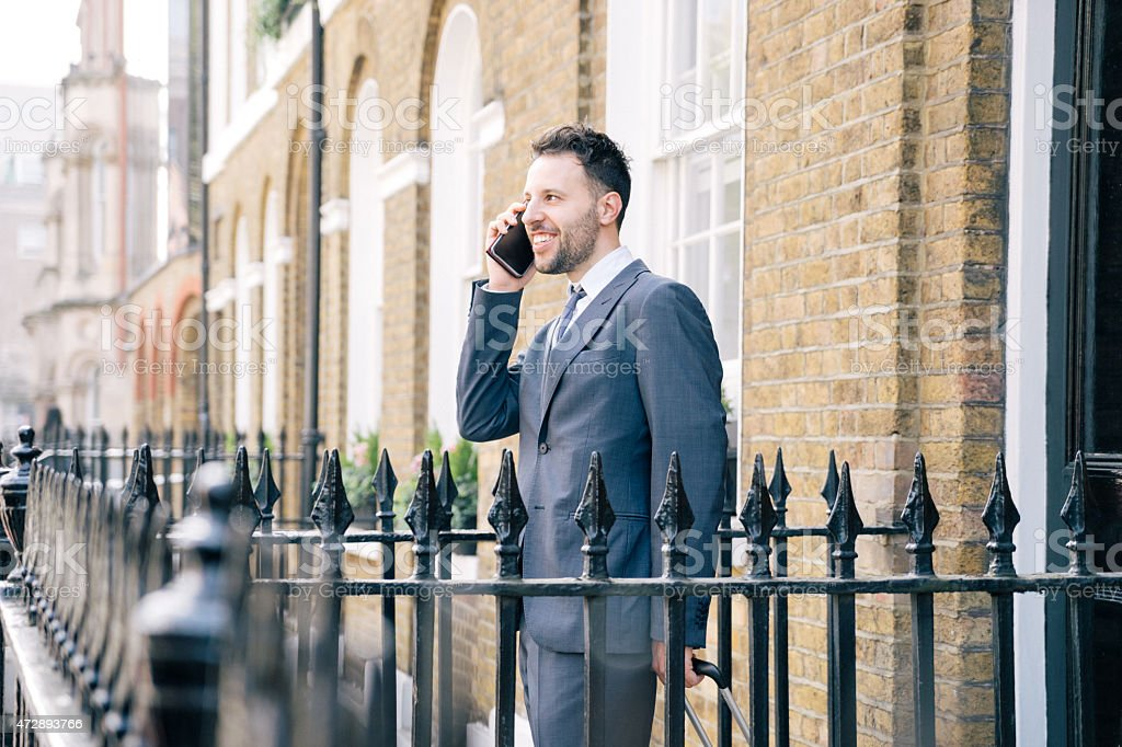 Businessman On The Phone Leaving Home In The Morning stock photo
