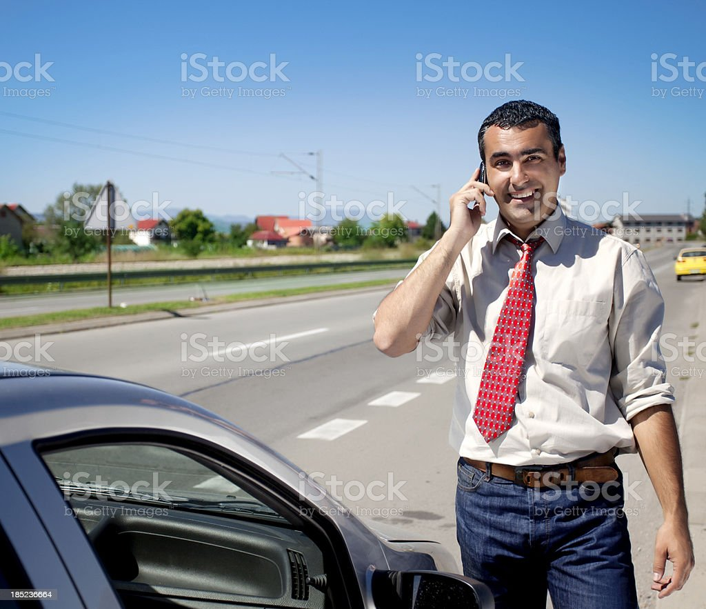 Businessman on the phone next to car royalty-free stock photo